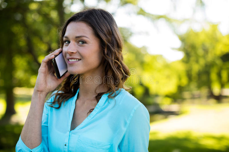 Woman talking on mobile phone in park stock photography