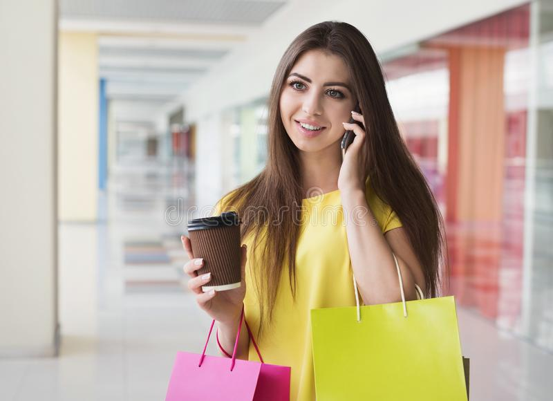 Woman talking on mobile phone while shopping in mall royalty free stock image
