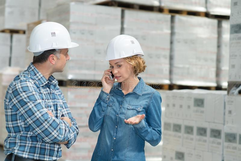 Woman talking on mobile-phone while standing next to manager stock photos