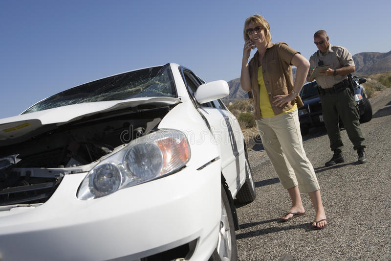 Woman Talking On Mobile Phone With Traffic Cop Writing Ticket On Street stock images