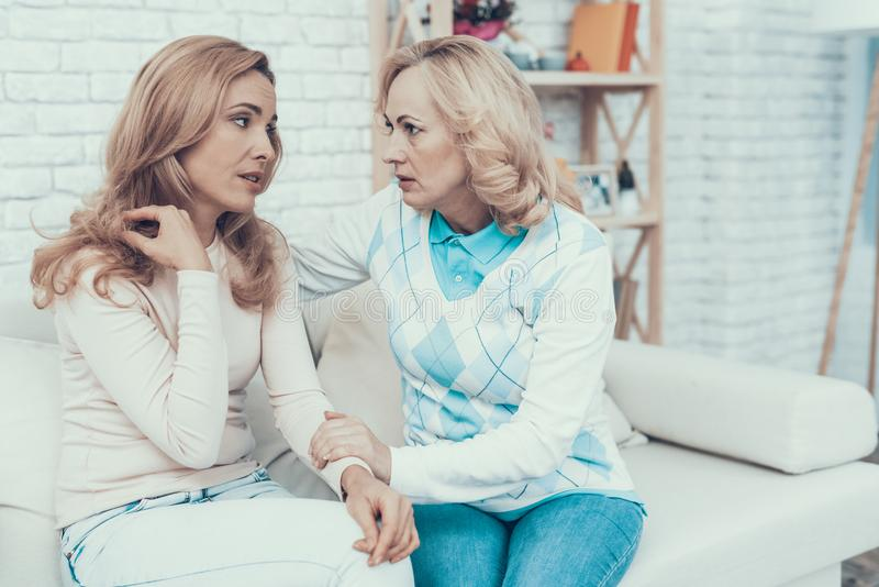 Woman Talking with Mother Sitting on White Sofa. Mother with Daughter. Talking Women. Sitting on Sofa. Conversation at Home. Discussion between People. Upset royalty free stock image