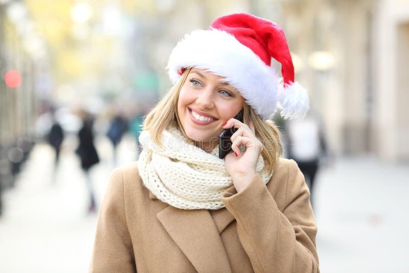 Woman talking on phone on christmas on the street. Happy woman wearing a santa hat talking on phone on christmas on the street stock images