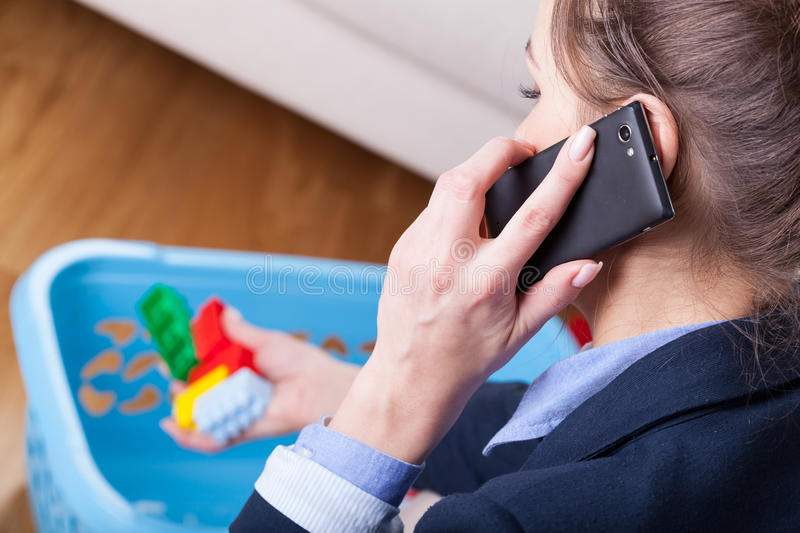 Woman talking on phone and cleaning up kids toys. Close-up of a woman talking on phone and cleaning up kids toys royalty free stock photography