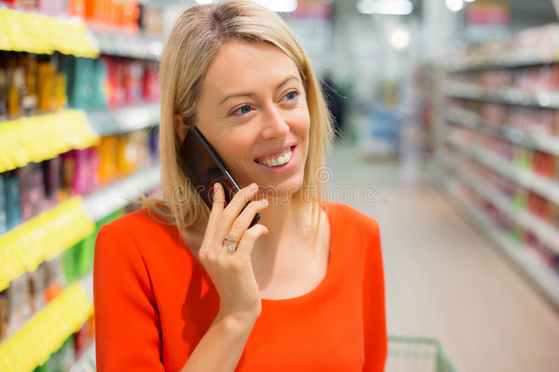 Woman talking on the phone in grocery store. Woman talking on the phone in store stock image