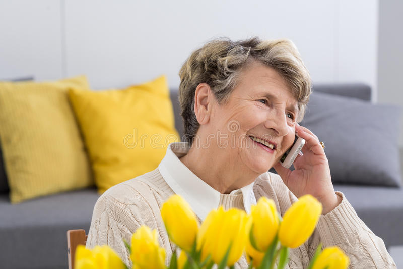Woman talking on the phone. Happy senior woman talking on the phone in the living room royalty free stock image