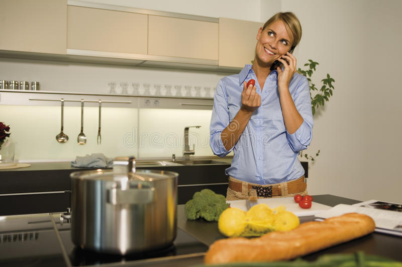 A woman talking on the phone in the kitchen. A smiling woman talking on the phone in the kitchen royalty free stock photo