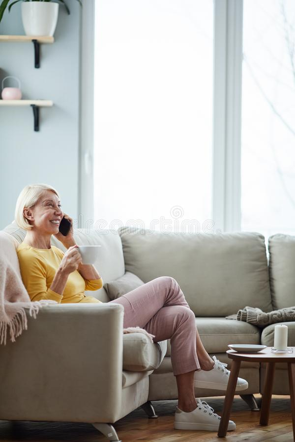 Woman talking on phone in living room stock image