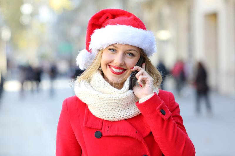 Woman talking on phone looking at you on christmas. Front view portrait of a happy woman talking on phone looking at you on christmas in the street stock image