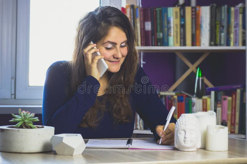 Woman talking on the phone sitting at a table. On the background of a bookcase royalty free stock photos