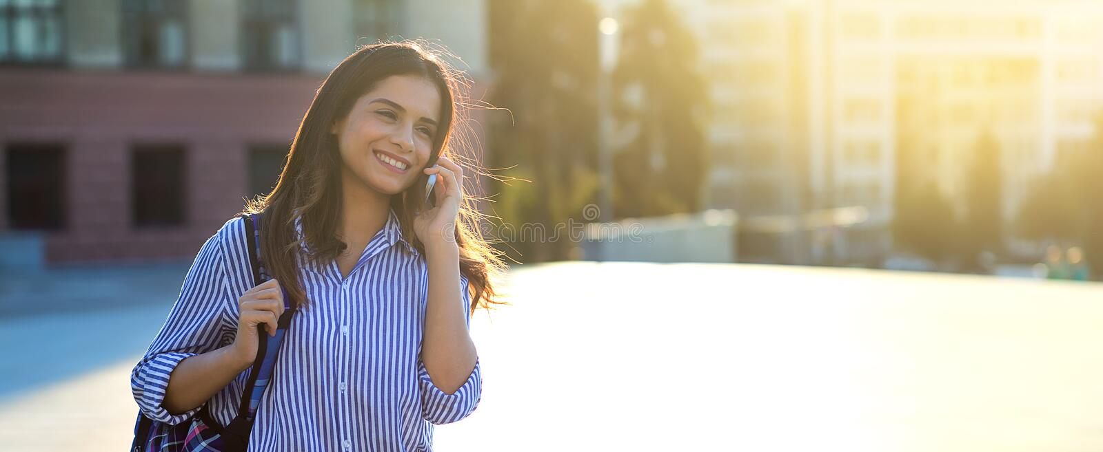 Woman talking by phone and smiling while walking along the streets with sunlight on her face and copy space stock photos