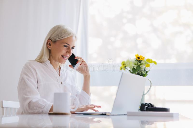 Woman talking on the phone, using laptop royalty free stock image