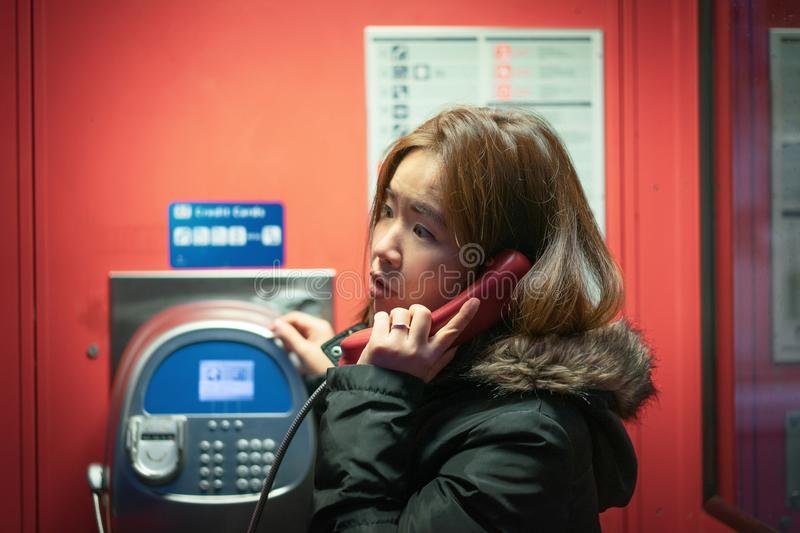 A girl is talking on a public telephone at night on the street. stock images