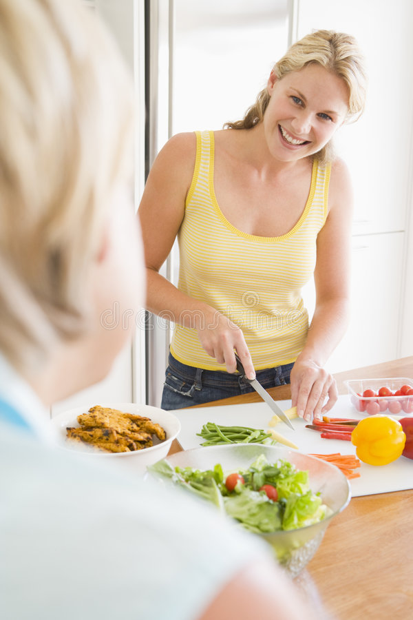 Woman Talking To Friend While Preparing Meal Stock Photography