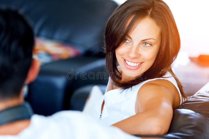 Woman talking to her husband sitting at home. Woman sitting on the sofa and chatting to her husband royalty free stock photos