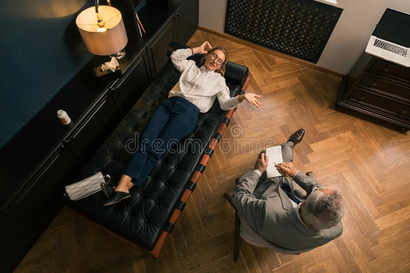 Woman talking to her psychotherapist in his office royalty free stock images