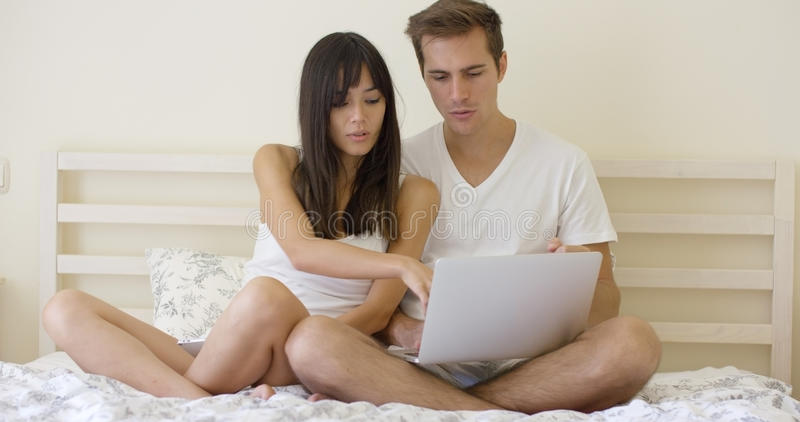 Woman talking to man using laptop while in bed. Smiling young long haired women showing something to handsome men on laptop while in bed royalty free stock photos