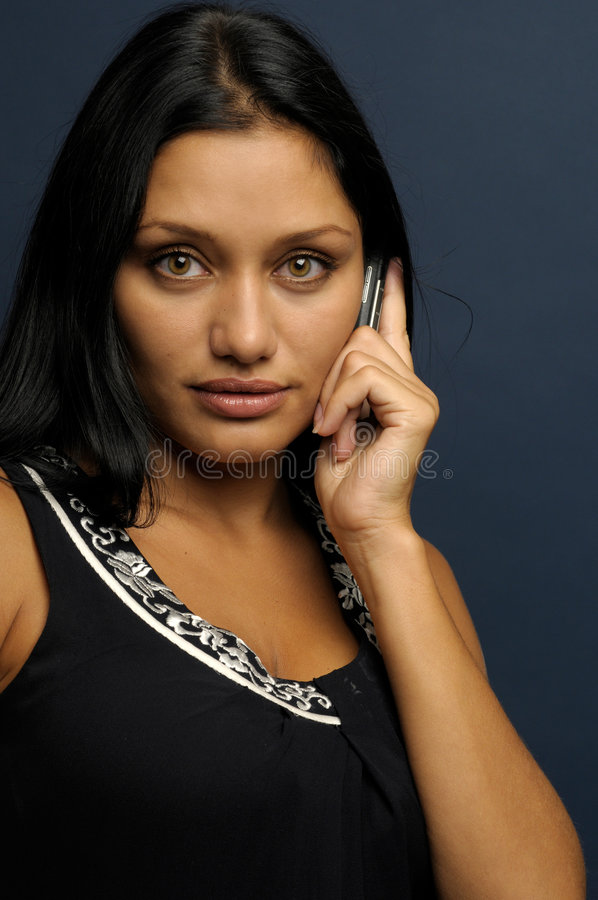 Woman is talking to phone. Beautiful exotic woman with seductive looking and long hair stock image