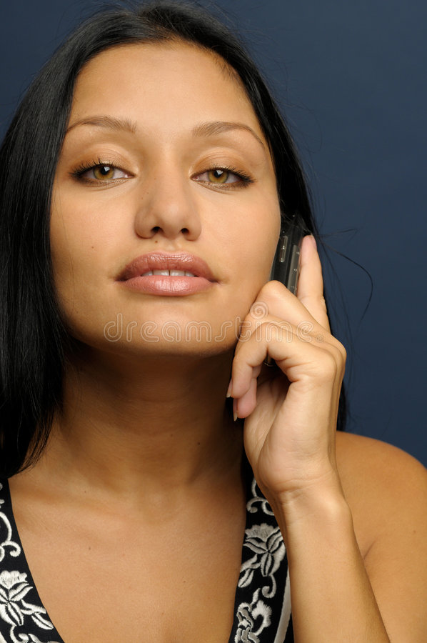 Woman is talking to phone. Beautiful exotic woman with seductive looking and long hair royalty free stock photos