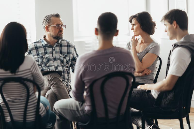 Woman talking to psychotherapist in support group for ACOA. Woman talking to professional psychotherapist in support group for ACOA royalty free stock images