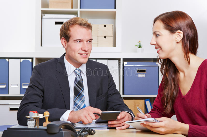 Woman talking to tax consultant. Smiling women talking to tax consultant in his office royalty free stock image