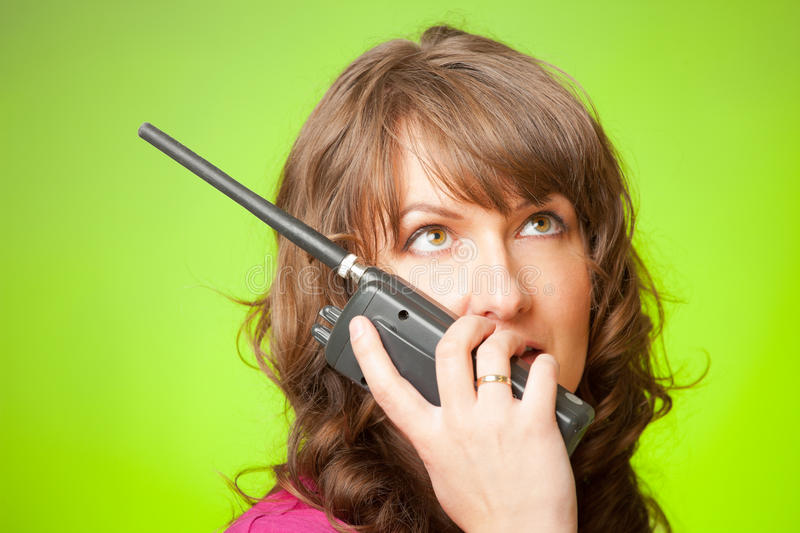 Woman talking on the walkie-talkie. Beautiful woman talking on the walkie-talkie over green background stock images