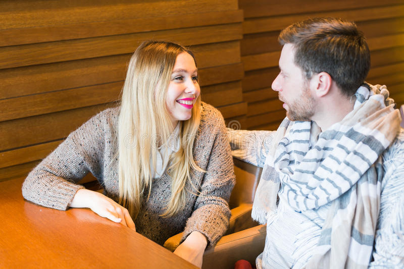 Woman talks with man sitting at the table in coffee house royalty free stock photos