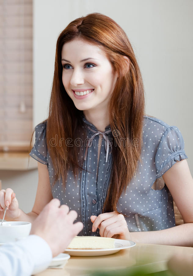 Woman talks with someone at the cafeteria royalty free stock image
