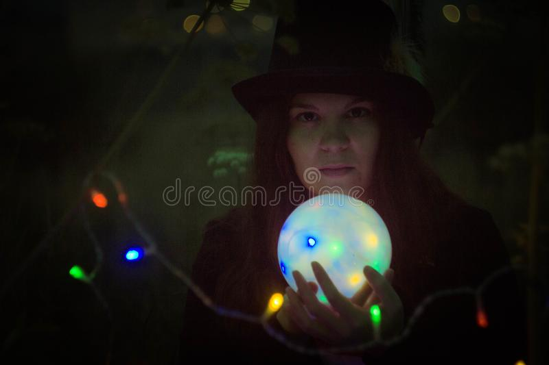 A woman in a tall hat with a glowing ball stock images