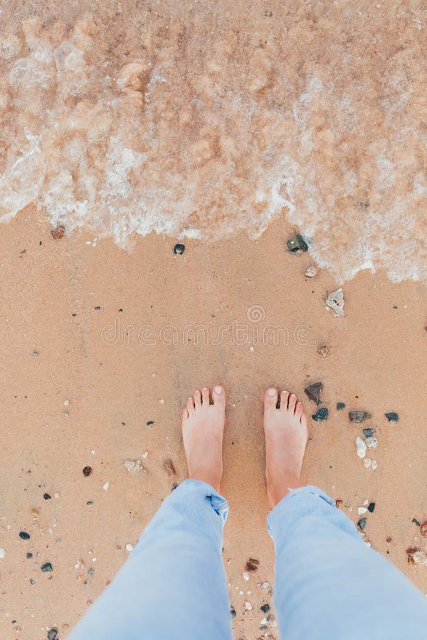 Woman tanned legs on sand beach stock image