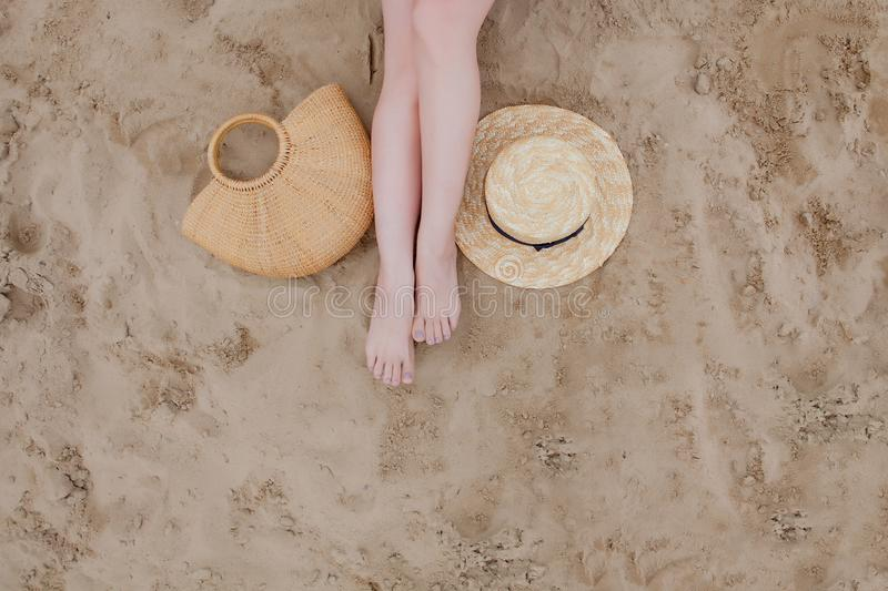 Woman tanned legs, straw hat and bag on sand beach. Travel concept. Relaxing at a beach, with your feet on the sand royalty free stock photos
