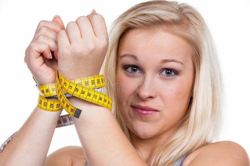 Woman with tape measure before the next diet. A young woman with a tape measure before the next diet. removing fast and royalty free stock photo