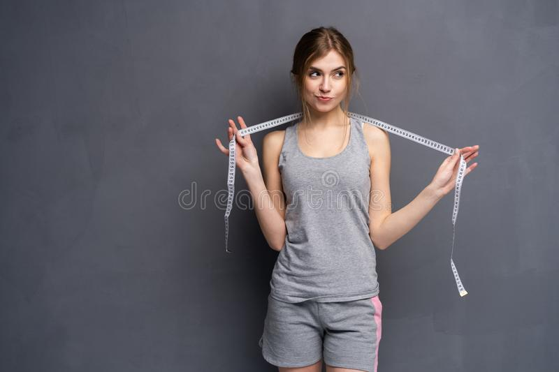 Woman and tape measure. Young, sporty, fit and beautiful girl with the measuring tape. royalty free stock photography