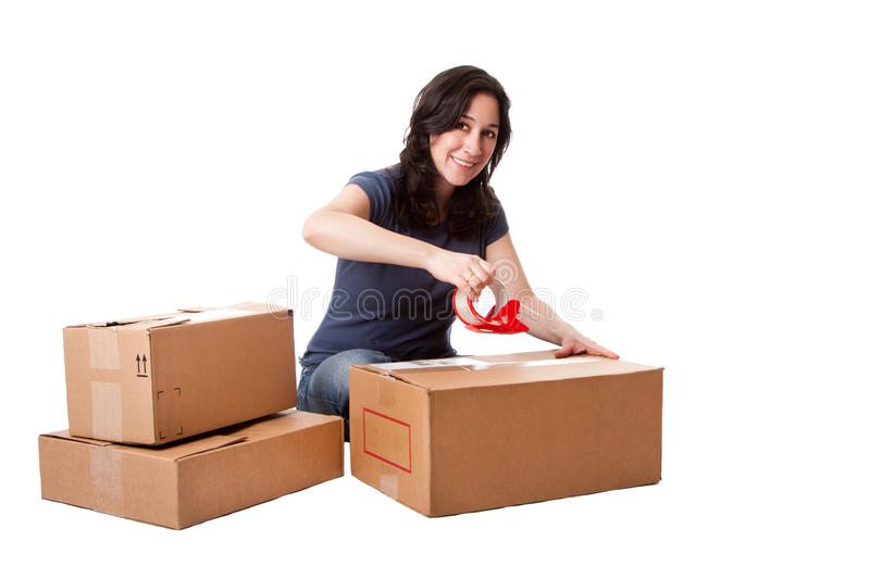 Woman taping moving storage boxes. Attractive happy beautiful woman putting tape on cardboard moving storage boxes parcels preparing for mail, isolated royalty free stock photography