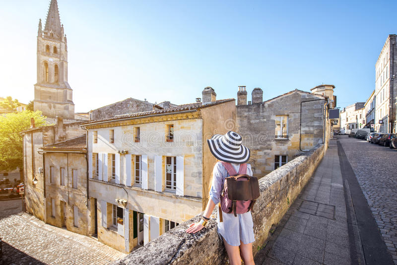 Woman tarveling in Saint Emilion village, France. Young woman tourist walking old street at the famous Saint Emilion village in Bordeaux region in France royalty free stock images