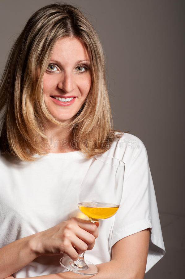 Woman tastes white wine and smile stock images