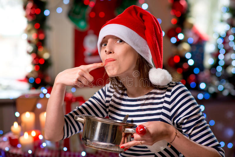 Woman tasting something tasty on Christmas stock photo