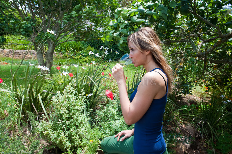 Woman tasting white wine. In the garden stock photography