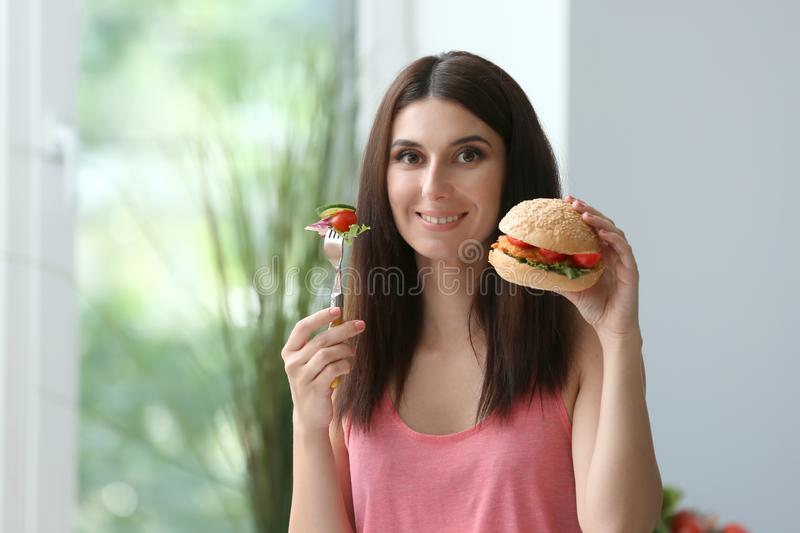 Woman with tasty burger and fork with sliced vegetables indoors. Choice between healthy and unhealthy food stock photos