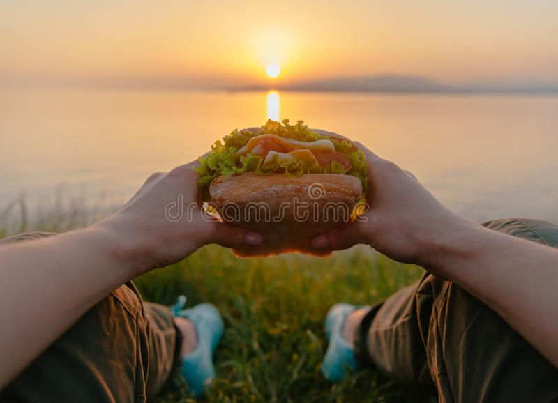 Woman with tasty burger by the sea, point of view. royalty free stock images