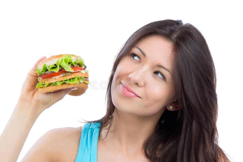 Woman with tasty fast food unhealthy burger in hand to eat. Young woman with tasty fast food unhealthy burger in hand to eat isolated on a white background royalty free stock photo