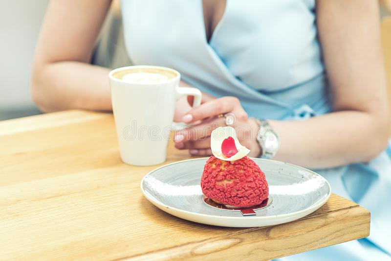 Woman with tasty piece of cake and cup of coffee in cafe close up stock image
