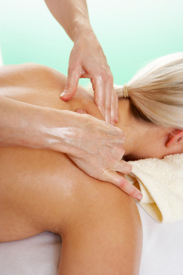 Woman with tattoo having shoulder massage royalty free stock photography