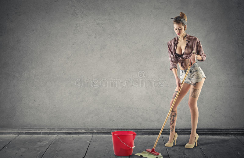 Woman with tattoos cleaning the floor stock photo