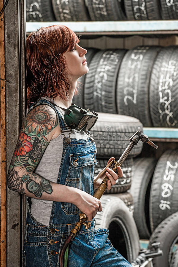 Woman with tattoos holding welding torch stock photo