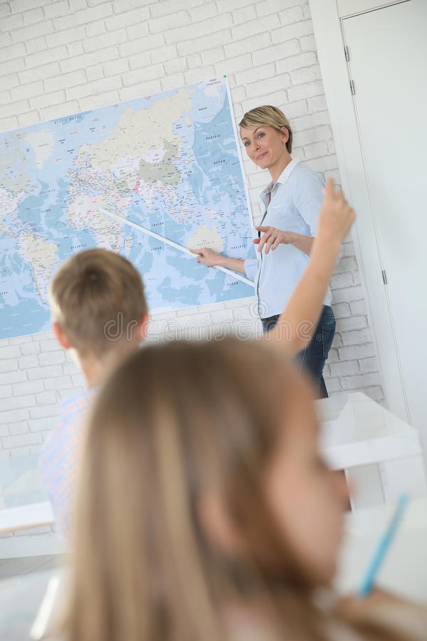 Woman teacher in classroom teaching geography royalty free stock image
