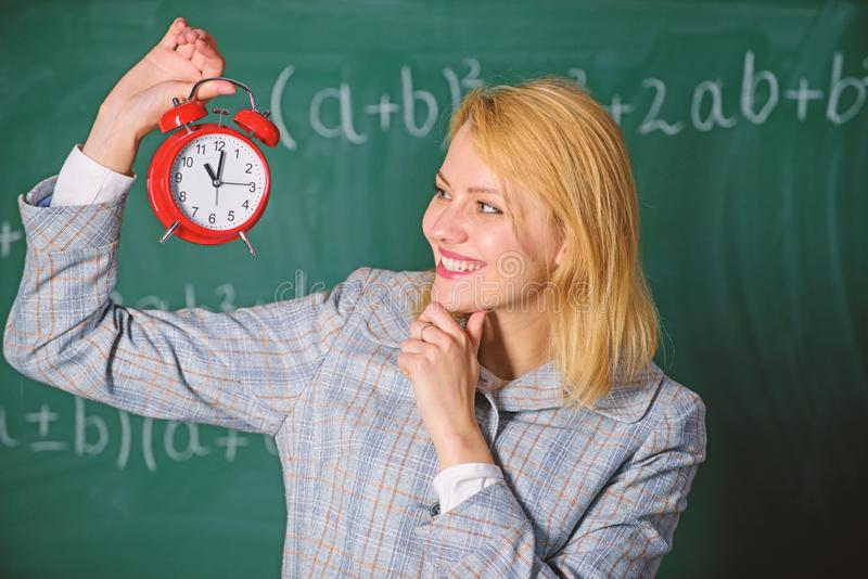 Woman teacher hold alarm clock. Girl school lecturer. What time is it. Lessons schedule. Welcome teacher school year royalty free stock photo