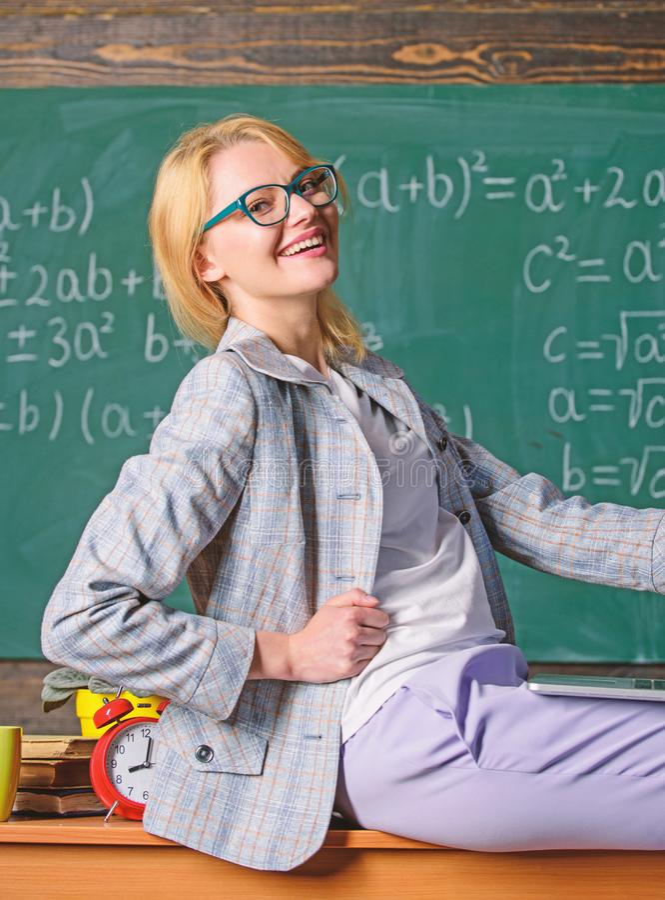 Woman teacher hold laptop sit table classroom chalkboard background. Teacher of modern generation. Influence non formal stock photos