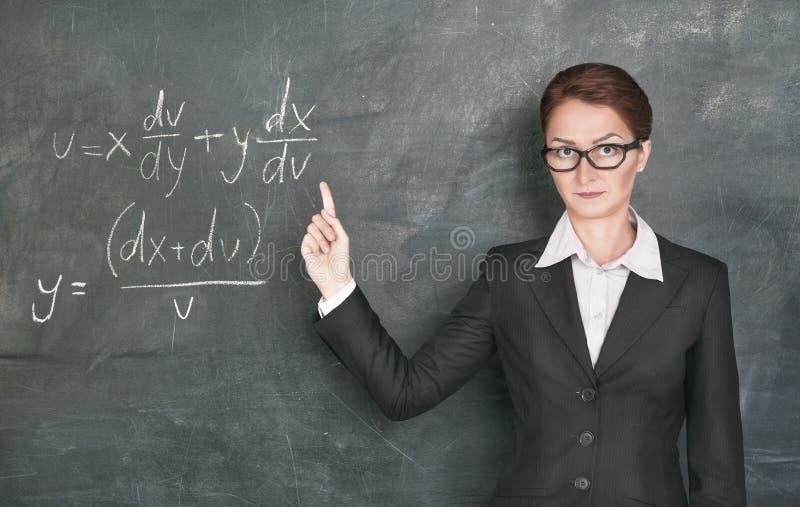 Woman teacher teaching maths. Woman teacher in glasses teaching maths and showing finger stock photo
