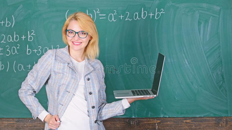 Woman teacher wear eyeglasses holds laptop surfing internet. Educator smart clever lady with modern laptop surfing royalty free stock photos
