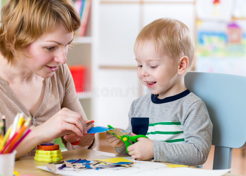 Woman teaches child handcraft at kindergarten or playschool or home stock photography